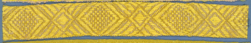 Yellow and pink trimming fragment in a design of alternating large and small lozenges.