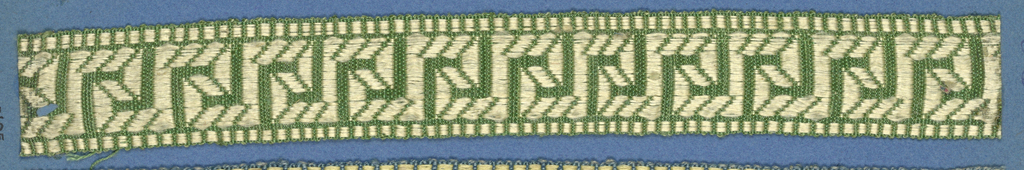Green and cream trimming fragment in a design of a Greek fret worked in diagonal lines.
