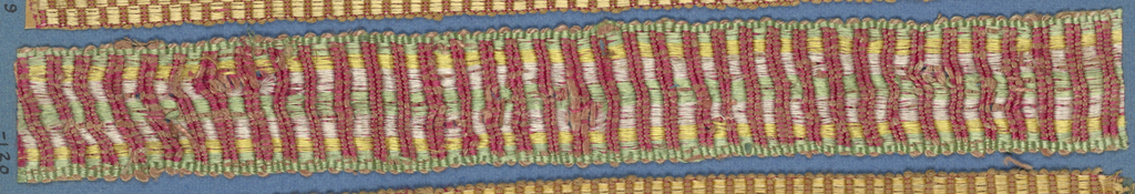 Trimming fragment in a striped design of red alternating with stripes of green, yellow and white.