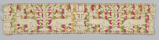 Fragment of a woven band or border with narrow dentelle on long edges. White stags alternate with vases and flowering trees, against a ground which is striped in red, green and yellow.