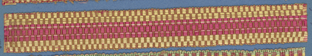 Red and tan trimming fragment in a checkerboard design arranged to form a red stripe between two yellow.
