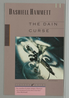 Lower portion of cover, square photographic image of champagne glass with metal syringe lying next to it on flat surface on which upside down, black and white film projection of a woman's face is being shown. Author's name in black text along upper left portion of cover on lavender-mauve colored ground. Directly above right of photograph, two lines of black text containing title which have horizontal lines extending to right edge above text, all on laveder-mauve colored ground. Directly below left edge of photograph, Vintage Crime logo in black text with small silhouette of gun and horizontal line above logo and silhouette. Below Vintage Crime logo, thin blue band above thick pink band with three lines of book review in black text. Two short vertical seafoam green lines near upper right corner extending from horizontal edge. Along upper left vertical edge of cover, thin black band with thin vertical orange line along right edge of band, all on lavender-mauve background.