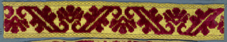 Trimming fragment in a design of flowers separated by leaves ending in scrolls. In red cut velvet on a yellow ground.