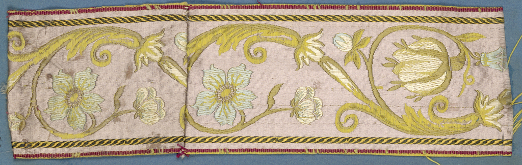 Lavender, blue, white, yellow and green trimming fragment in an incomplete design showing flowers, leaves and scrolls.