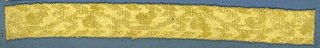 Yellow trimming fragment in a design of a scrolling stem with acorns.