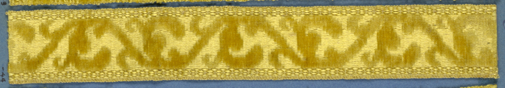 Yellow trimming fragment in a design of a scrolling stem with conventionalized leaves.