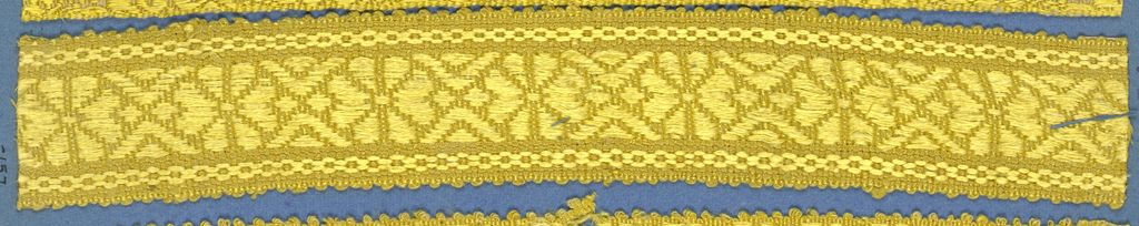 Yellow trimming fragment in a design of a central band with eight-petal flowers separated by chevrons between chain borders; picot edges.