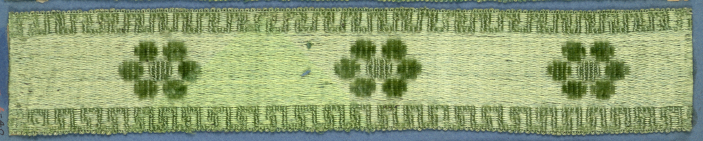 Green trimming fragment with a design of open flowers widely spaced between fret borders.