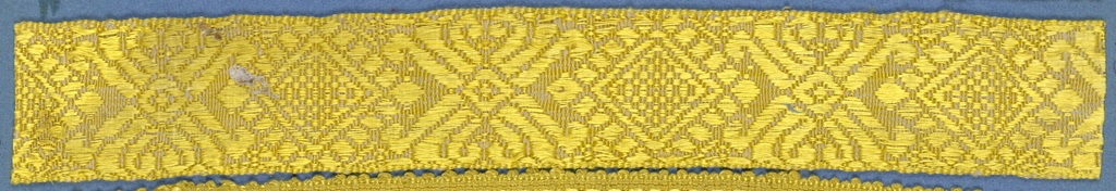 Yellow trimming fragment in a design of alternately placed lozenge and cross motifs.