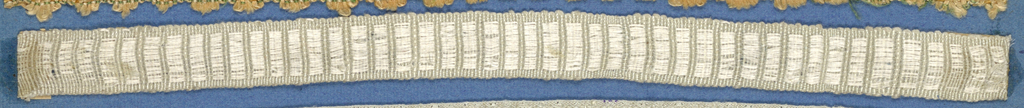 White trimming fragment in a design of satin and plain weave stripes.