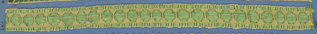 Green and yellow trimming fragment in a design of green discs set between a border of dashed lines.
