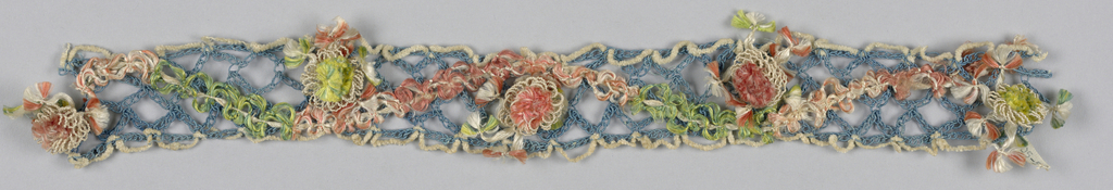 Diamond-shaped openwork band of loosely chained blue cords sewn with serpentines of colored knotted silk floss. Floral pompom of silk floss and silk cord centered in each scallop. Edging in scalloped white chenille.