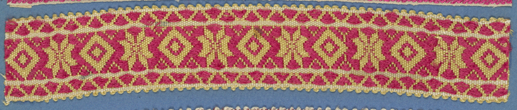 Red, yellow and white trimming fragment in a design of eight-pointed stars alternating with lozenges between borders of triangles; picot edges.