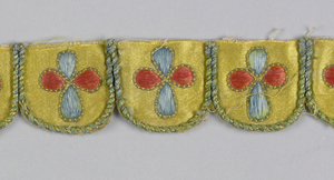 Fragment of an embroidered and scalloped trimming. Yellow satin cut into scallops is edged with green and gold cord and embroidered in the center with a four petal flower head pattern in orange and blue silk thread.