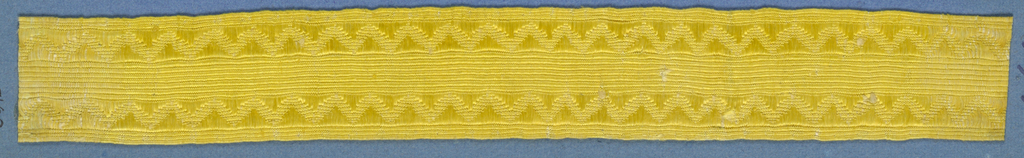 Yellow trimming fragment in a design of sawtooth borders with broken diagonal lines in between.