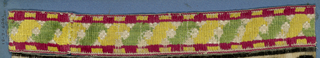 Red, yellow, green and white trimming fragment in a design of green and yellow leaves placed diagonally and bordered with red and yellow bands.