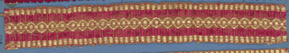 Red and tan trimming fragment showing a central band ornamented with touching rings and placed between red stripes.