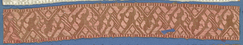 Pink trimming fragment in a design of an ornamented zigzag band.