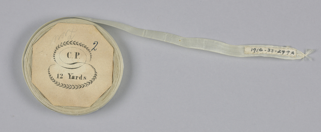 White tape or seam binding on a flat wooden spool.