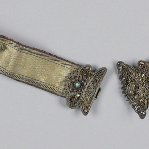 Woman's belt made of gold and black ribbon with a silver filigree buckle decorated with turquoise and other materials. Lined in magenta silk.