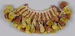 Yellow, brown and red fringe with a heading and skirt threads tied in loops; every fourth supporting a tassel with wired ornaments.
