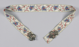 White ribbon with blue and red floral design. Silver buckle has a design of conventionalized flowers.