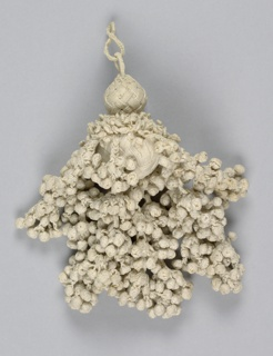 White linen tassel with two wooden balls forming the base. These are braided over with linen yarns worked in groups of four yarns for a basket-weave effect. From the lower ball hang numerous small braids terminating in clusters of tiny braided balls.