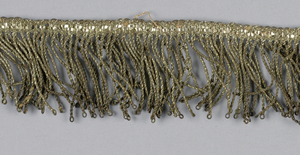 Fringe of metallic thread with a thin woven heading and twisted fringe.