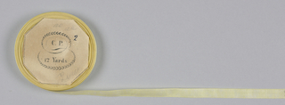 Yellow tape or seam binding on a flat wooden spool.