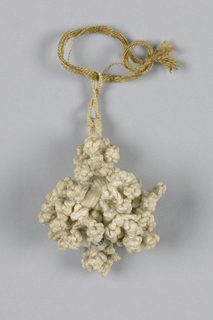 Small linen tassel, braided and knotted. Short double loops attached to center ball to which are attached short knottings.