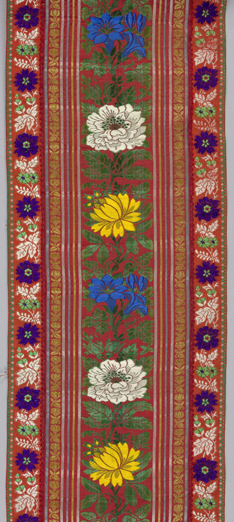 The width is composed of three ribbons sewn together.  The broader central ribbon is dull red and has vertical stripes in blue, white, and yellow and green foliage repeated vertically.  The narrow ribbons on either side are a brighter red and have flowers and foliage in purple, green, and white.