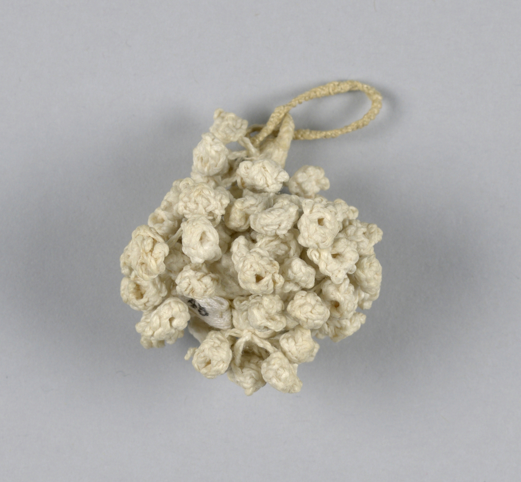 Tiny tassel of linen, braided and knotted. Double loops attached to short stem terminating in small round ball which is entirely covered with clusters made of small knots.