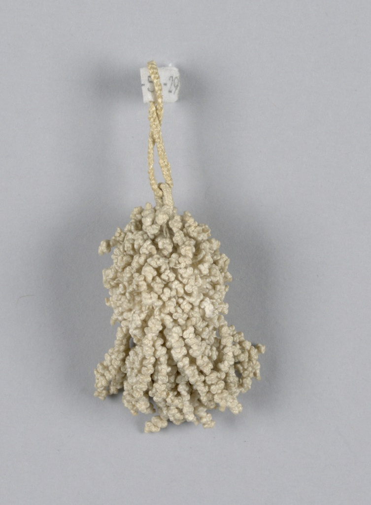 Small linen tassel, braided and knotted. Round center ball solidly covered with tiny knottings. Single loop.