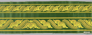 Border fragment with two horizontal rows of alternating trefoil and willow branch in brown and yellow on green satin ground.