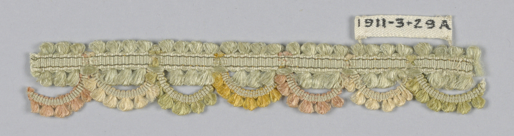 Woven heading with loops on either side. On one edge, heading is scalloped with multicolored loops extending below it.