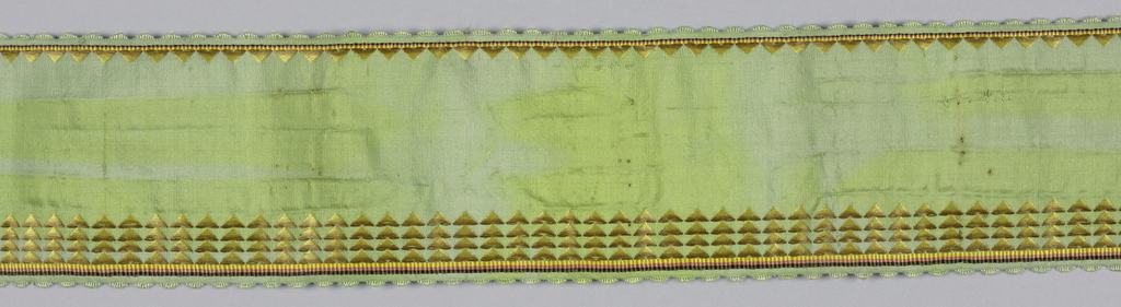Green ribbon with narrow and wide borders of triangular forms in gold silk. Scalloped picot edge.