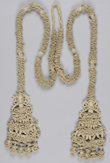A long cord completely covered with knotting and braiding, to which are attached two equally large tassels arranged in tiers of elaborate knotting and braiding.