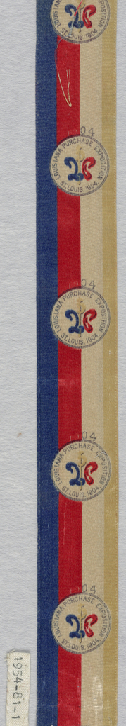"Fragment of a ribbon commemorating the Louisiana Purchase Exposition held in St. Louis in 1904. Ribbon has vertical stripes of blue, red, white and off-white. Circles outlined in blue appear at regular intervals and read: ""Louisiana Purchase Exposition St. Louis 1904."""