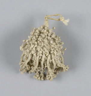 Linen tassel, braided and knotted. Single loop attached to tiny braided stem which in turn is attached to round ball. Letter completely covered with numerous tiny knottings.