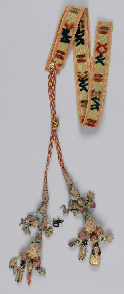 Pair of elaborate tassels in needlework, attached to narrow silk bands with cut velvet pattern. From main tassels of colored silk and metal threads hang many small figures, animals and birds. One figure in bright red, modern and made in Guatemala.