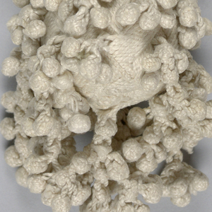 White linen tassel with long braided stem attached to a pear-shaped base. Core is braided over with linen yarns worked in groups of seven for a basket-weave effect. Around the base hang tiny braided balls and from the bottom hang a few clusters of the tiny braided balls.
