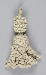 White linen tassel with single loop and two balls forming the base. These are covered in braiding, connected by braided stem, and are covered in tiny braided balls. Strings of these balls also hang from the larger (bottom) center ball.