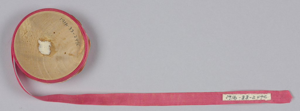 Rose-colored tape or seam binding on a flat wooden spool.