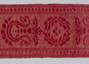 Fragment from curtain (rings still at top) of warm red, hard-surfaced wool, stamped in barely visible design of large all-over floral motifs. Bordered along one side by woven linen-and-silk strip in wreath and anthemioh design, also red.