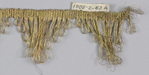 Gold fringe with a plain-woven heading and a scalloped edge of looped threads.