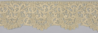 Fragment of a border or flounce of ivory cotton net heavily embroidered with ivory silk floss and imitation pearls. Design of scrolls and modified rinceau with deep scallops repeated along lower edge.