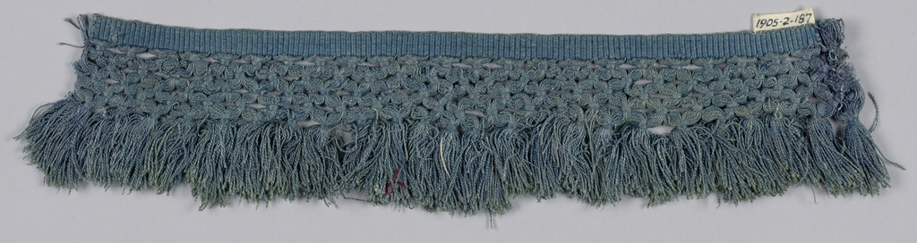 Blue fringe with a plain weave heading. Trellis band above slightly scalloped skirt threads.