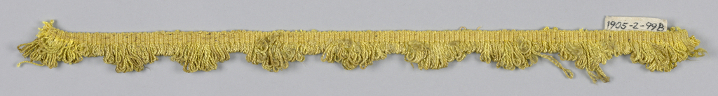 Yellow fringe with a plain-woven heading and a skirt of looped threads graduated to form scallops.