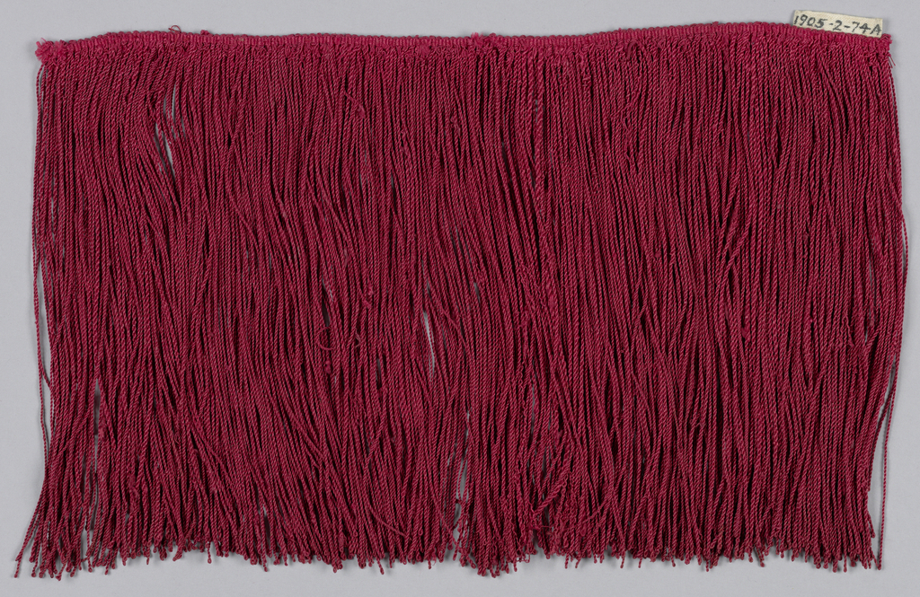 Fringe with a narrow woven heading and a skirt of red silk threads looped and twisted.