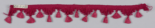 Red fringe with a heading and looped skirt threads forming a pointed edge; ornamented with tufts.